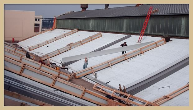 Uncrating metal roofing panels prior to installation and mechanical seaming.